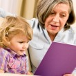 Grandmother and granddaughter read book together - Stock Photo