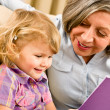 Grandmother and granddaughter read book together - Stockfoto