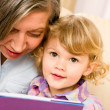 Grandmother and granddaughter read book together — Stock Photo #8943470