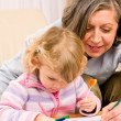 Cute little girl drawing with grandmother at home — Stockfoto