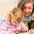 Cute little girl drawing with grandmother at home — ストック写真