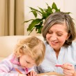Little girl with grandmother drawing together — Stock Photo #8943512