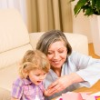 Stock Photo: Little girl with grandmother play glue paper