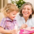 Little girl with grandmother play glue paper - Stock Photo