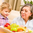 Grandmother with granddaughter eat fruit at home — Stock Photo