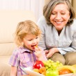 Little girl eat apricot fruit with grandmother — Stock Photo #8943565