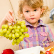 Cute little girl hold grapes fruit bowl — Stock Photo