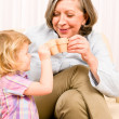 Grandmother with granddaughter drink tiny cups — Stock Photo #8943595