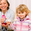 Little girl with grandmother play bubble blower - Stock Photo