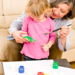 Little girl with grandmother play paint handprints — Stockfoto #8943652