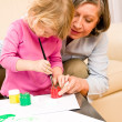 Little girl with grandmother play paint handprints - Stockfoto
