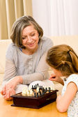 Grandmother and granddaughter play chess together — Foto Stock