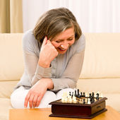 Senior woman play chess happy sit on sofa — Stock Photo