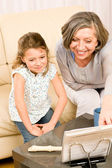 Grandmother teach young girl learn music notes — Stock Photo