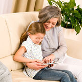 Grandmother with granddaughter use touch tablet — Stock Photo