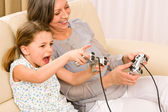 Grandmother and granddaughter play computer game — Stock Photo