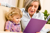Grandmother and granddaughter read book together — Stok fotoğraf