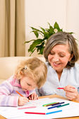 Little girl with grandmother drawing together — Stock Photo