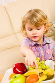 Little girl wants fruit pointing at banana — Stock Photo