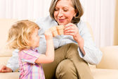Grandmother with granddaughter drink tiny cups — Stock Photo