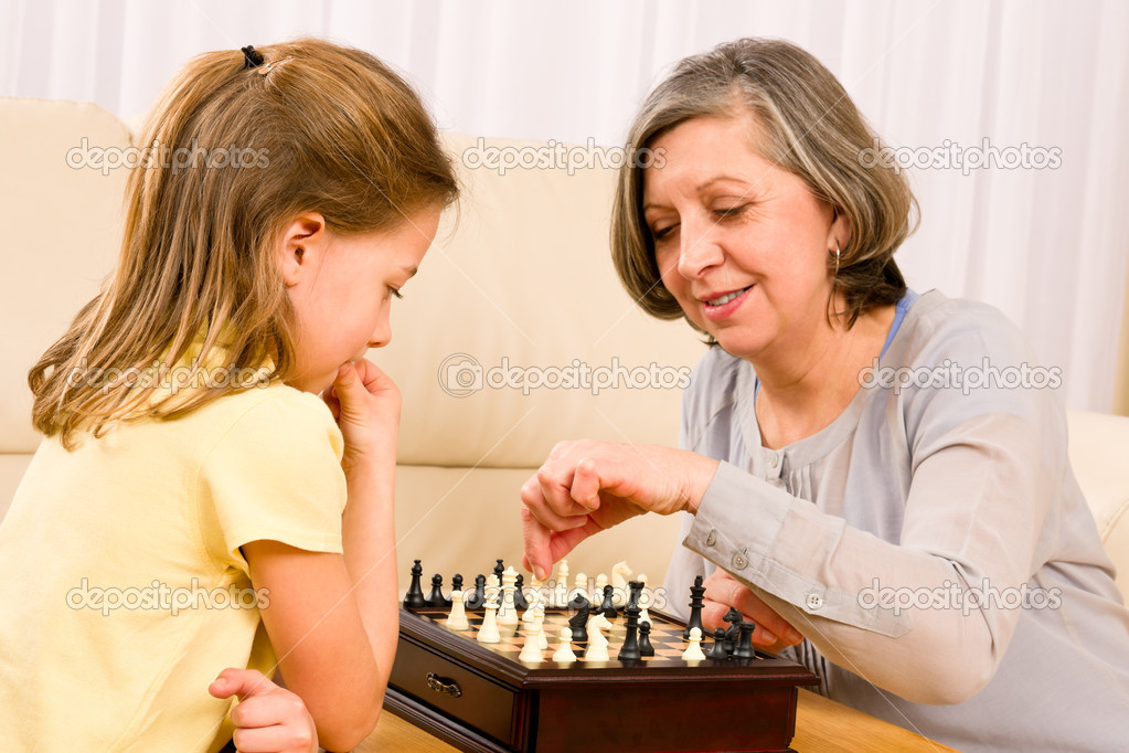Grandmother and young girl playing chess together at home — Stock Photo #8943214