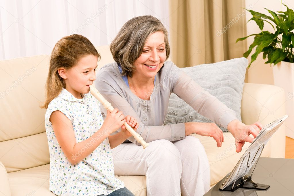 Grandmother teach young girl to play flute happy sitting on sofa — Stock Photo #8943255