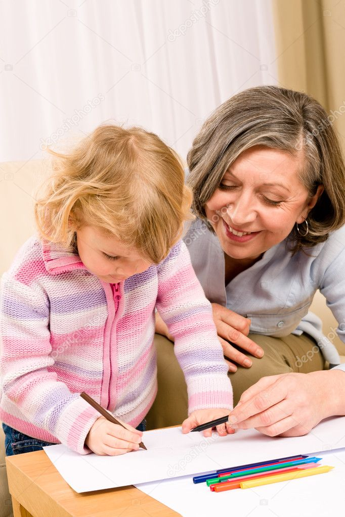 Grandmother and little girl drawing together with pencils at home  Stock Photo #8943475