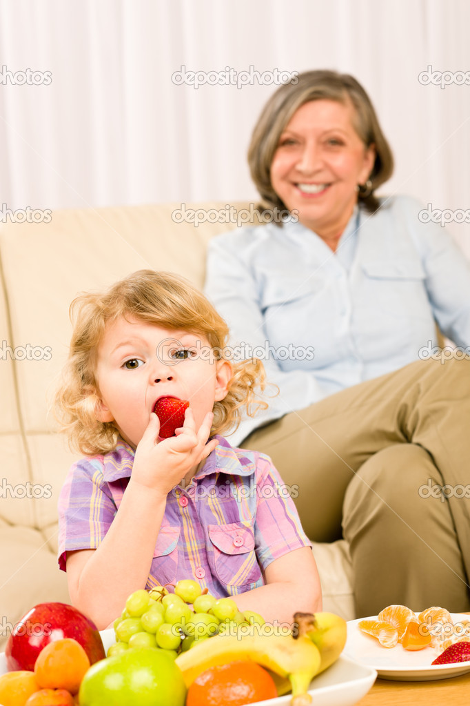 Little girl eat strawberry fruit with grandmother relaxing on sofa — Stock Photo #8943537