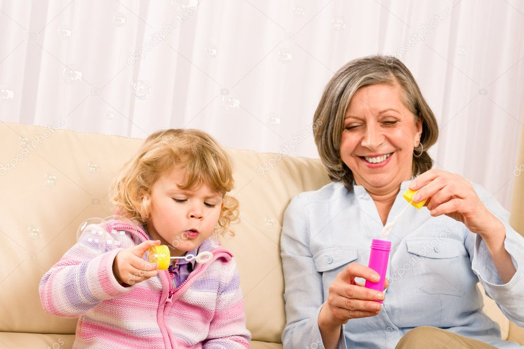 Little granddaughter with grandmother make bubble blower play happy together — Stock Photo #8943613
