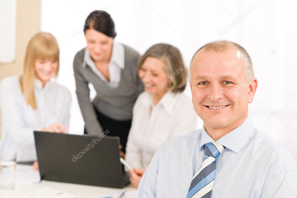Smiling businessman during team meeting with colleagues looking at laptop — Stock Photo #9036740