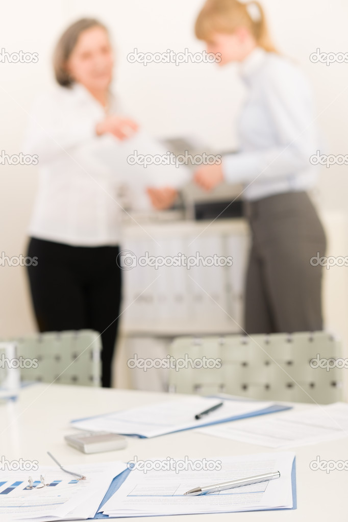 Office supply on table - two business women out of focus — Stock Photo #9036779