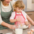 Stock Photo: Child girl and grandmother baking cake