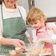 Stock Photo: Grandmother and granddaughter prepare dough