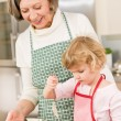 Woman and little girl baking cupcakes together — Stock Photo #9547881