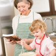 Funny little girl baking cupcake with grandma — Stock Photo