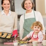 Three generations of women baking in kitchen — Stock Photo