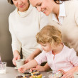 Stock Photo: Daughter and mother decorating cupcakes sprinkles