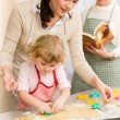 Little girl with mother cutting out cookies — Stock Photo