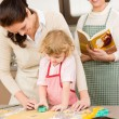 Stock Photo: Little girl with mother cutting out cookies