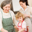 Little girl with grandmother cutting out cookies — Foto de Stock