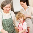 Little girl with grandmother cutting out cookies — Stock Photo
