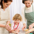 Little girl with mother cutting out cookies — Stock Photo #9547954