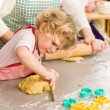 Little girl cutting dough for cookies — Stock Photo