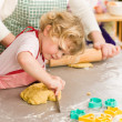 Royalty-Free Stock Photo: Little girl cutting dough for cookies