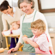 Grandmother with little girl prepare dough - Stock Photo