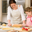 Mother and daughter making apple tart together - Stock Photo