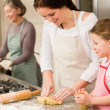 3 generations of women baking apple pies — Stock Photo