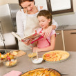 Mother and daughter look baking cookbook — Foto de Stock