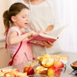 Mother and daughter look baking cookbook — Stock Photo #9548071