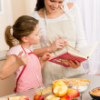 Mother and daughter look baking cookbook — Stock Photo #9548074